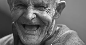 Fotografía en blanco y negro de un adulto mayor sonriendo.