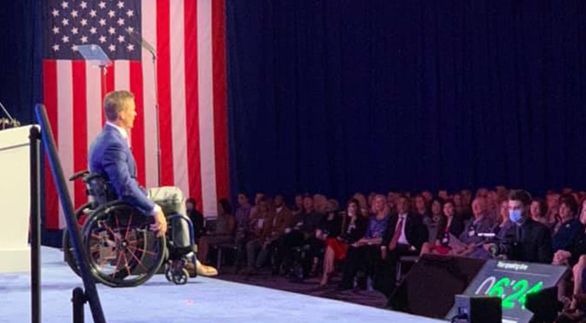 Fotografía de Madison sentado en su silla de ruedas, detrás de él la bandera de Estados Unidos y frente a él un grupo de personas viéndolo.