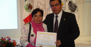 Fotografía de María Candelaria con una sudadera rosa sosteniendo un diploma con su mano derecha, junto a ella un hombre en traje negro y detrás de ellos la bandera de México.