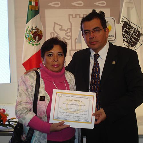 Fotografía de Maria Candelaria con una sudadera rosa sosteniendo un diploma con su mano derecha, junta a ella un hombre en traje negro y detrás de ellos la bandera de México.