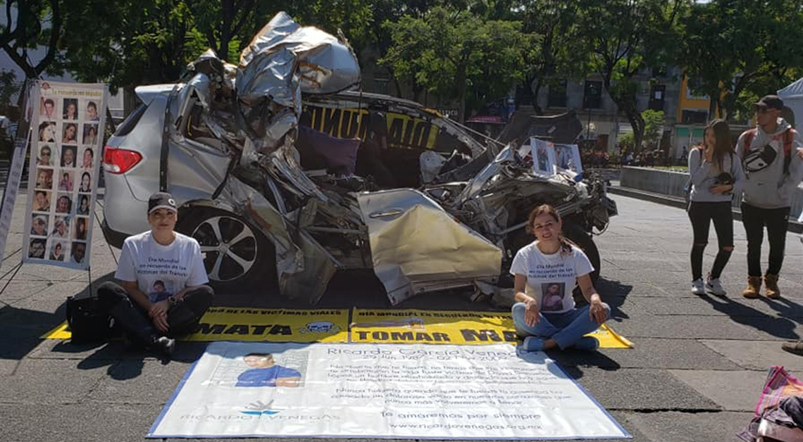 Fotografía de dos mujeres sentadas en el suelo, con las piernas cruzadas, detrás de ellas un carro chocado y sin puertas, en medio de ellas una manta blanca.