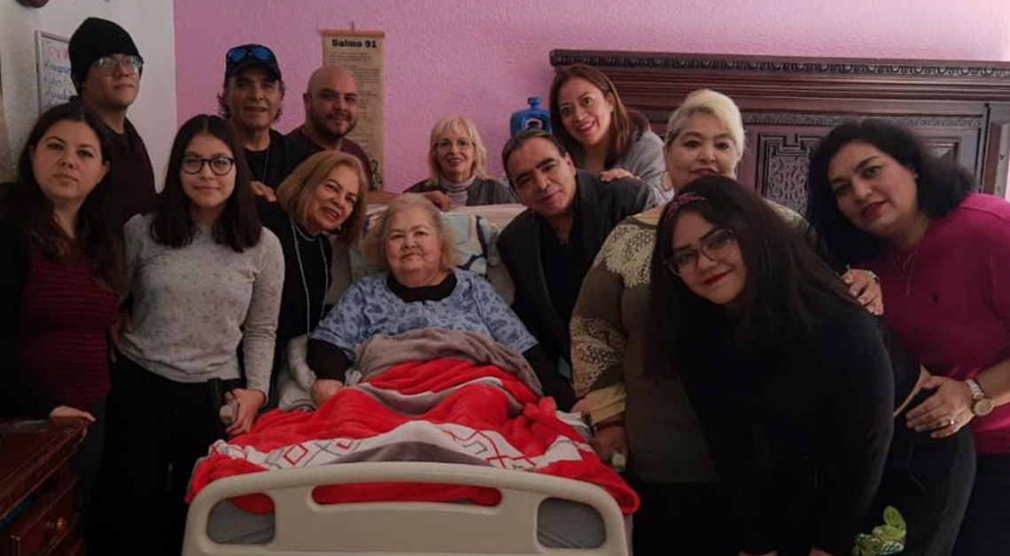 Fotografía de un grupo de personas al rededor de una cama donde esta acostada una señora, todos están sonriendo y ven hacia la cámara.