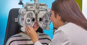 Fotografía de una doctora de espaldas haciendo un examen de la vista a una mujer.