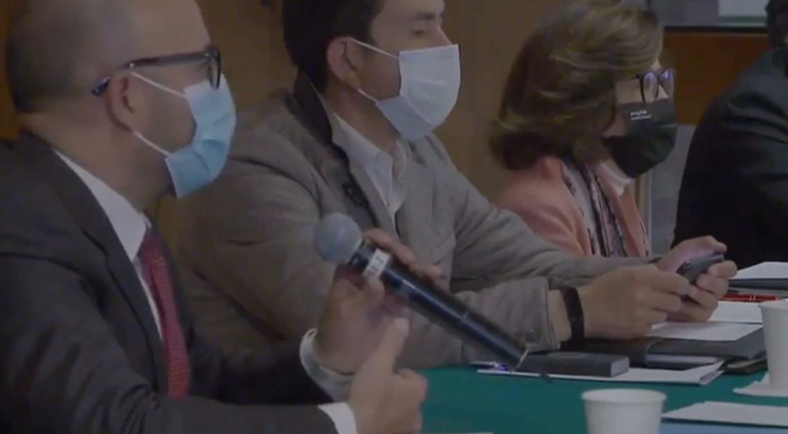 Fotografía de tres personas con cubrebocas sentadas frente a una mesa, dos hombres y una mujer, el primero tiene un micrófono en la mano, el segundo esta viendo su celular y la tercera ve al frente.
