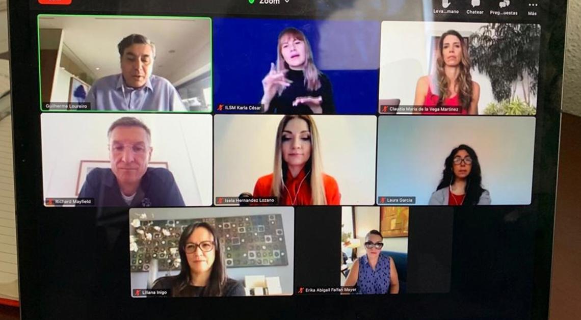 Fotografía de la pantalla de una tablet durante una llamada de zoom, ocho personas están en la llamada y en el centro una intérprete de lengua de señas.