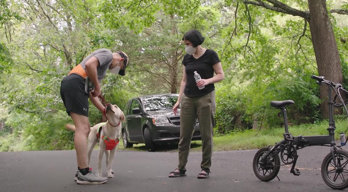Fotografía de Thomas con su perro guía y una mujer, él tiene puesto un short color negro con un cinturón color naranja y una playera deportiva color gris, su perro lleva un chale naranja, mientras que la mujer viste una blusa negra con un pantalón verde. Detrás de ellos una camioneta negra y una bicicleta.