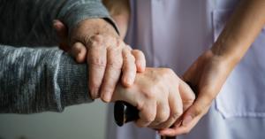 Fotografía de las manos de una persona mayor sobre bastón.