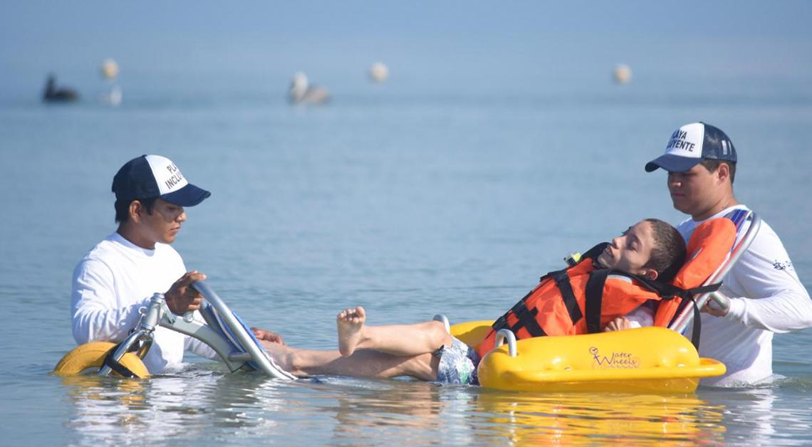 Fotografía de tres personas dentro del mar, dos de ellas vestidas con una playera blanca y una gorra azul ayudan a un hombre con discapacidad a flotar dentro del mar.