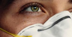 Fotografía del rostro de una mujer usando un cubrebocas blanco, tiene los ojos color verde y el cabello suelto.