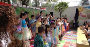 Fotografía de el patio de una escuela donde se encuentran los estudiantes disfrazados realizando una coreografía frente a los padres de familia.