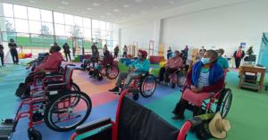 Fotografía de un salón donde se encuentran ocho personas sentadas en silla de ruedas, el piso es de colores y hay algunas sillas sin personas sentadas.