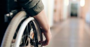 Fotografía de una mano sobre la rueda de una silla de ruedas.