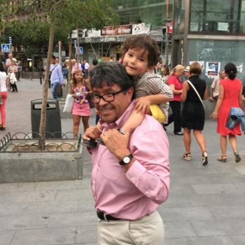 Fotografía del senador Ricardo con su nieto en los hombros, los dos están sonriendo para la fotografía. El lleva puesta una camisa color rosa y su nieto con una sudadera gris.
