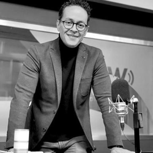 Fotografía en blanco y negro de Enrique detrás de un escritorio, lleva puesto un saco y esta sonriendo para la foto.