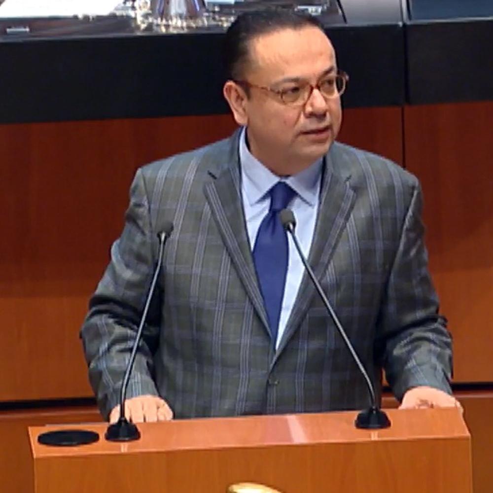 Fotografía del Senador parado detrás del estrado, frente a el un par de micrófonos. Viste un traje gris con una camisa azul.