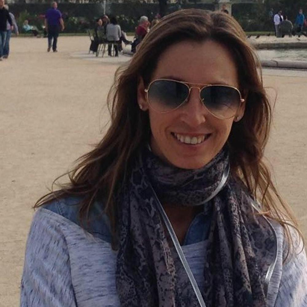 Fotografía del rostro de Karina sonriendo, lleva puestos unos lentes oscuros, una bufanda y una blusa gris.