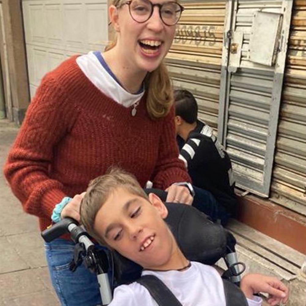 Fotografía de Mariana empujando a un joven con paralisis cerebral en su silla de ruedas, ambos riendo.