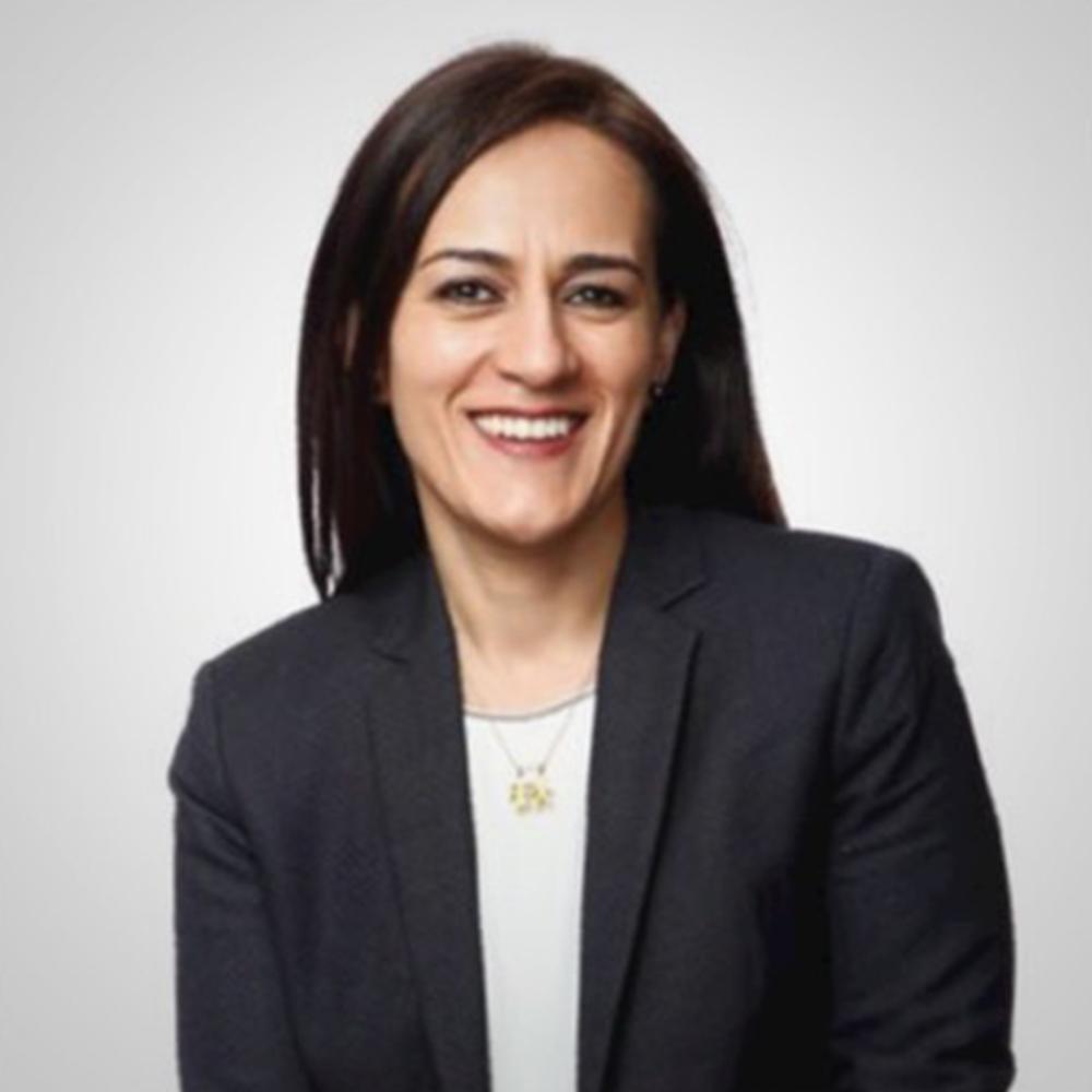 Fotografía del rostro de Mónica sonriendo, lleva puesto un saco negro y una blusa gris clara.