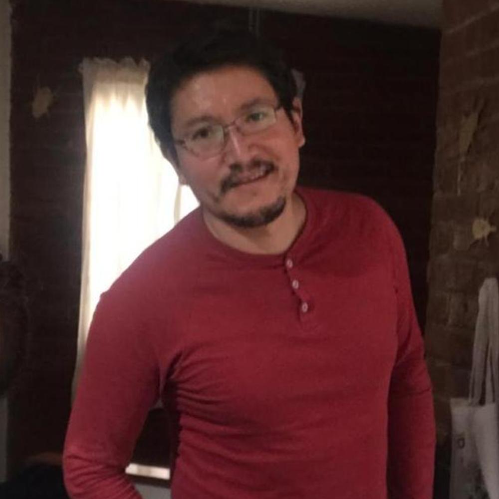 Fotografía del rostro de Victor sonriendo, lleva puesta una playera color roja.