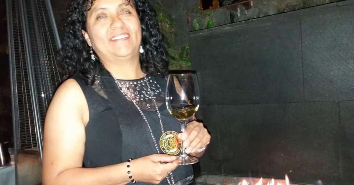 Fotografía de Naivi sonriendo, lleva puesto un vestido negro sin mangas y sostiene con ambas manos una copa de vino.