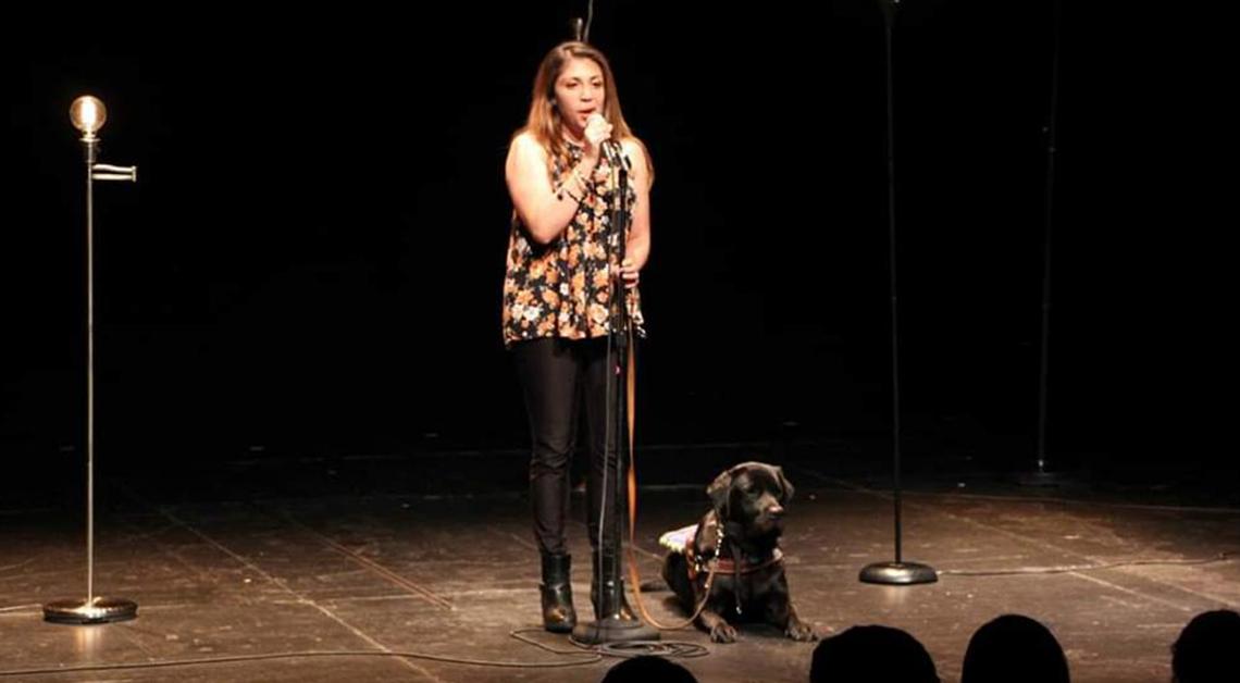 Fotografía de Erika de pie en un escenario, viste una blusa negra con un estampado de flores de colores y un pantalón negro. A su derecha está acostado un perro y frente a ella un micrófono.
