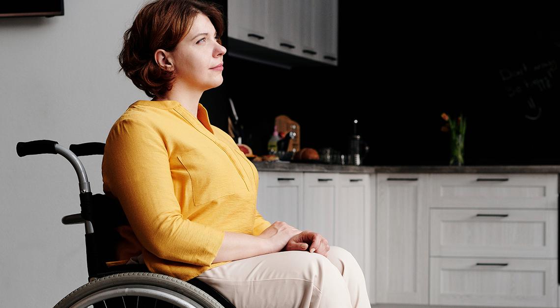 Fotografía de perfil de una mujer sentada en una silla de ruedas frente a su puerta, viste una blusa amarilla con un pantalón café.
