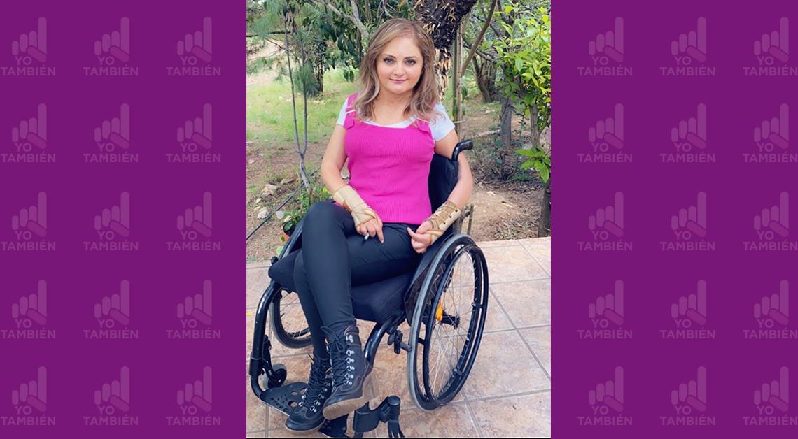 Fotografía de Claudia sentada en una silla de ruedas y viendo a la cámara, viste una blusa rosa con un pantalón negro.