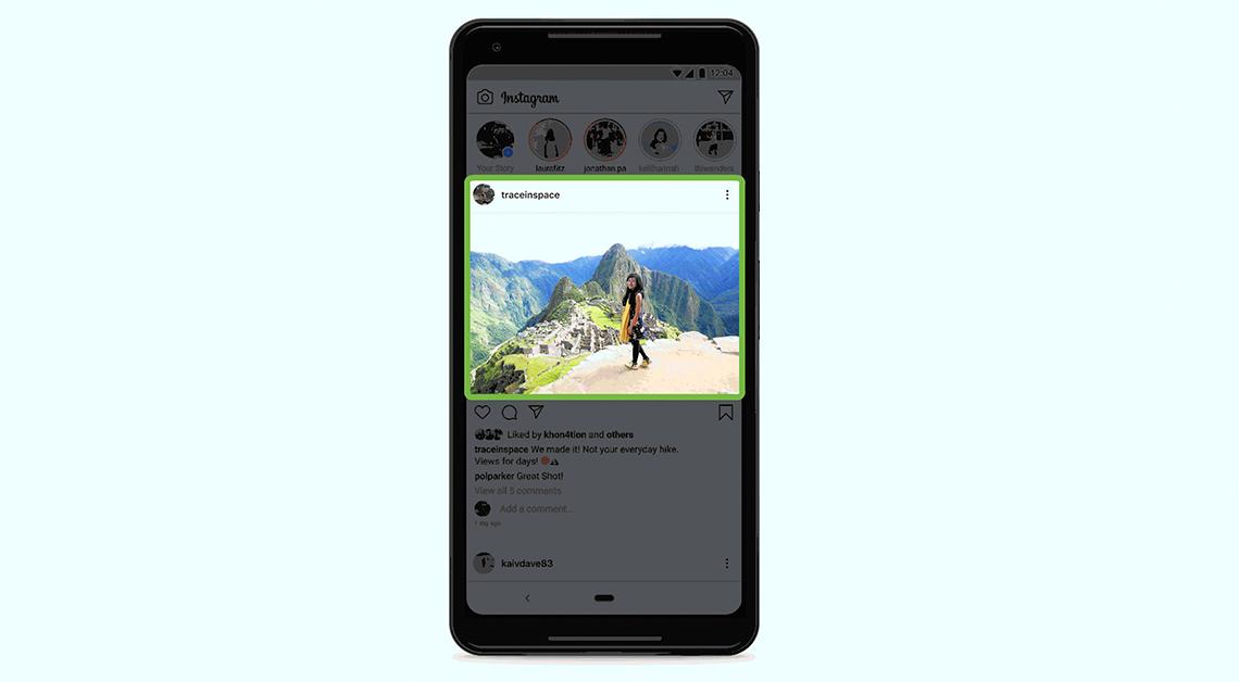 Fotografía de un teléfono celular con una foto en el centro, en ella una mujer está parada frente a una montaña, lleva puesto un pantalón de mezclilla, una blusa sin mangas negra y una bufanda amarilla.
