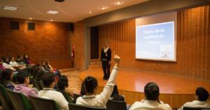 Fotografía de un salón de clases con paredes de ladrillo, al centro está la profesora, vestida con un pantalón negro, un suéter del mismo color y blusa blanca. Frente a ella hay una hilera de alumnos sentados, uno de ellos tiene el brazo levantado.