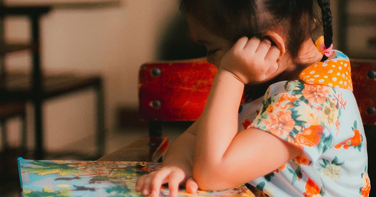 Fotografía de una niña con un vestido verde con un estampado de flores anaranjadas; está sentada en un pupitre con su mano derecha en una hoja de papel y con su cabeza recargada sobre su mano izquierda.