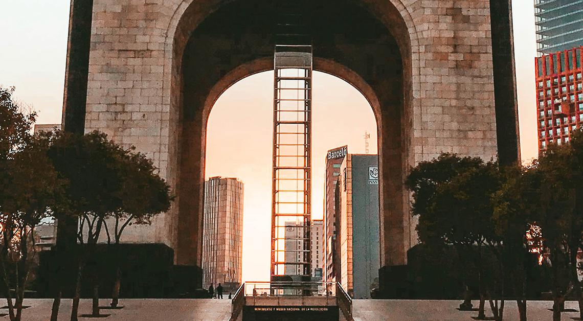 Fotografía de la base del monumento a la revolución con el amanecer detrás.