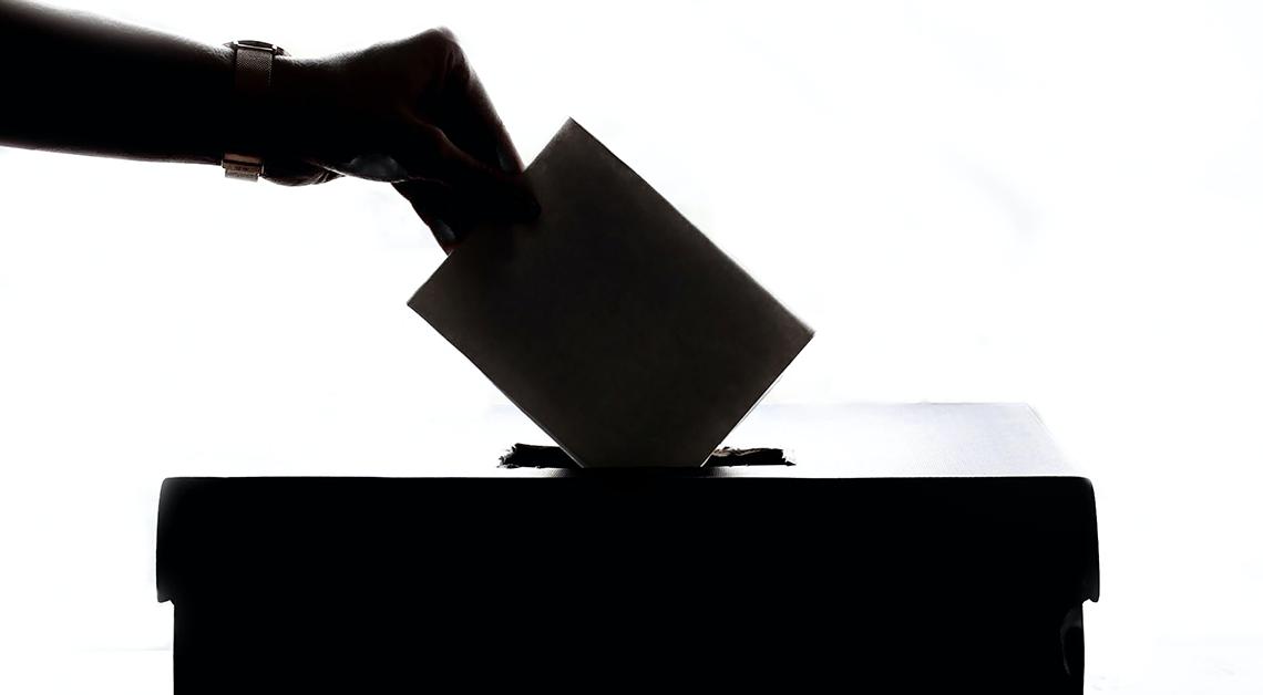 Fotografía en blanco y negro de una mano insertando una boleta electoral en una urna.