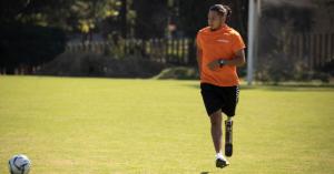 Fotografía de Gustavo en una cancha de futbol, está de frente corriendo hacia un balón que está frente a él. Lleva puesta una playera naranja y un short negro.