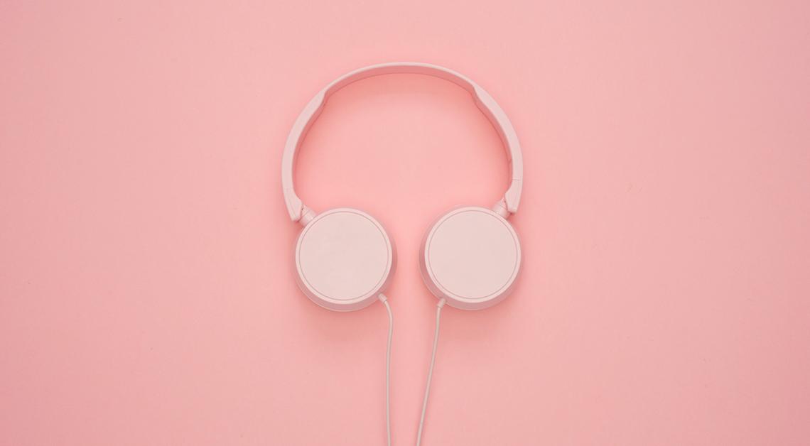 Fotografía de unos audífonos color rosa sobre una mesa.