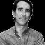 Fotografía de Gerardo Gaya a blanco y negro, un hombre de edad adulta que se encuentra sonriendo y utiliza una camisa con el primer botón de su camisa desabrochado.