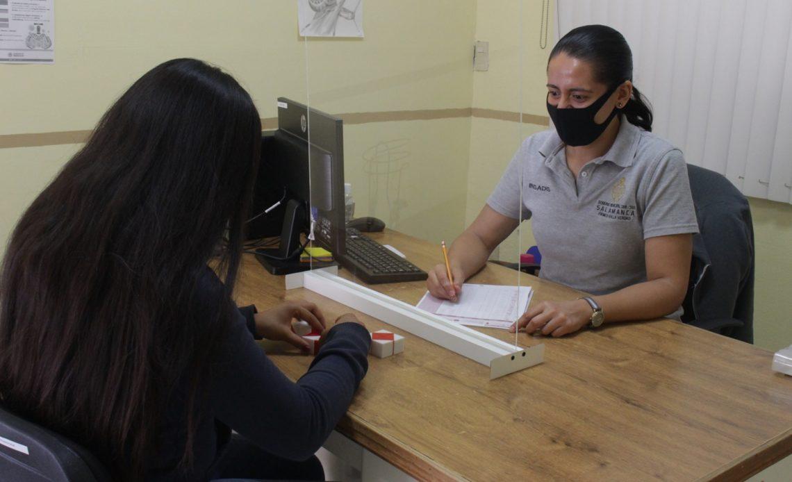 Fotografía del personal del Instituto Salmantino atendiendo a una persona con las debidas medidas de seguridad sanitaria.