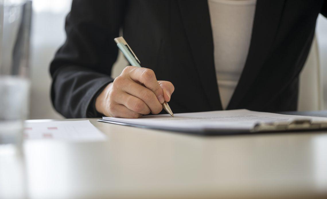 Mano de una mujer firmando un papel sobre una mesa color blanca.