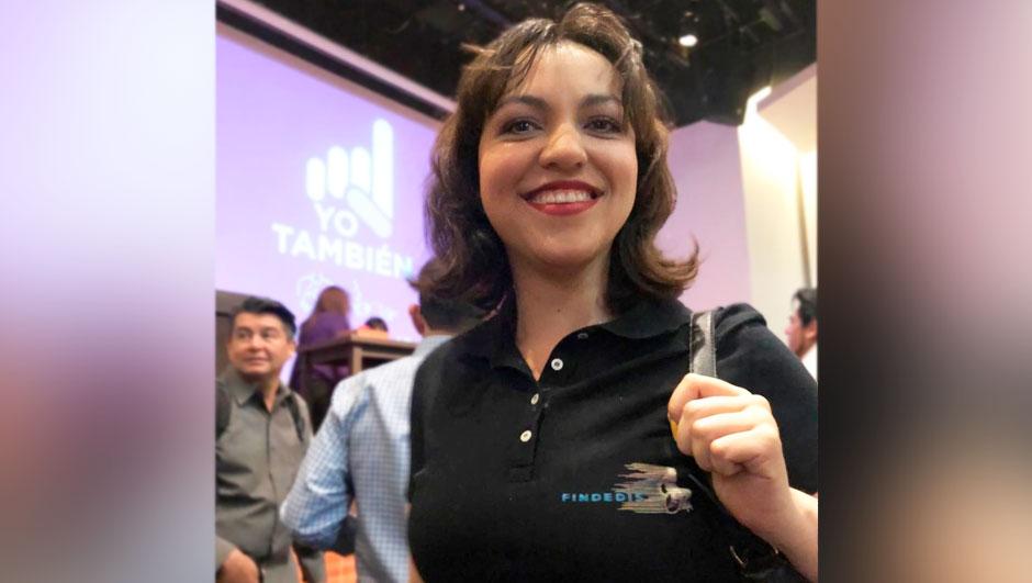 Fotografía de Marilú Castro, una mujer joven, con cabello castaño, corto a la altura de los hombros, se encuentra de pie y lleva puesta una playera color negro, con su mano izquierda sostiene la correa de su bolso. Detrás de ella aparece proyectado el logotipo de Yo También en una pantalla al fondo.