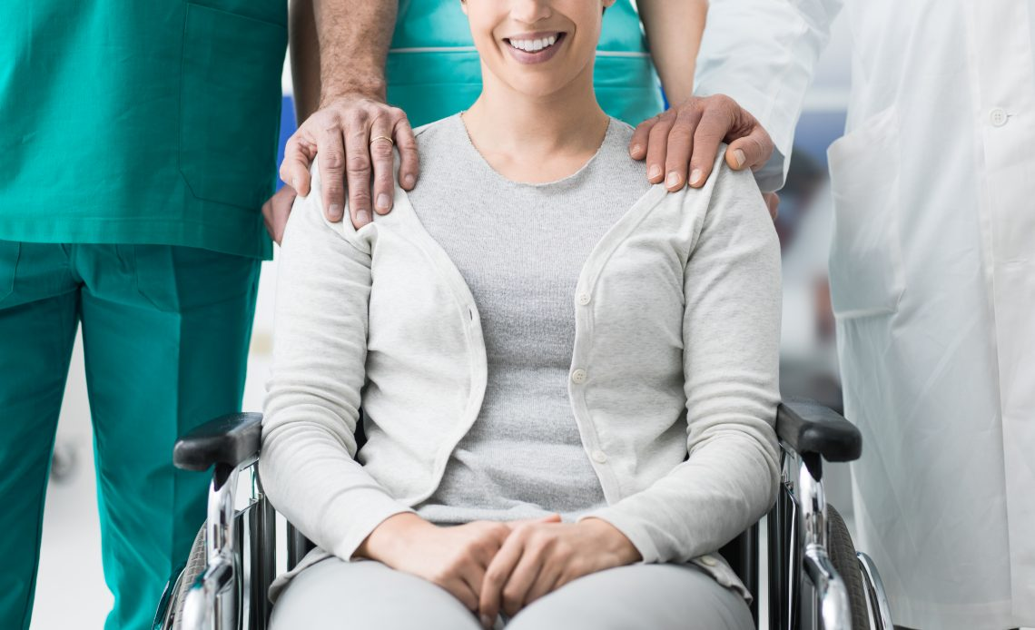 Fotografía de una señora de edad media sonriendo, sentada en silla de ruedas con playera gris, tiene la mano de un enfermero sobre su hombro derecho y la mano de un doctor sobre su brazo izquierdo.
