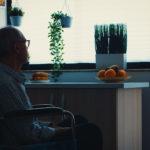 Fotografía de un hombre de edad adulta a contraluz frente a una ventada cuya expresión refleja soledad y tristeza.
