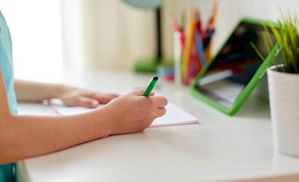 En la fotografía aparecen los brazos de una niña en clases en línea que escribe sobre el pupitre de su casa con una tableta electrónica al frente.