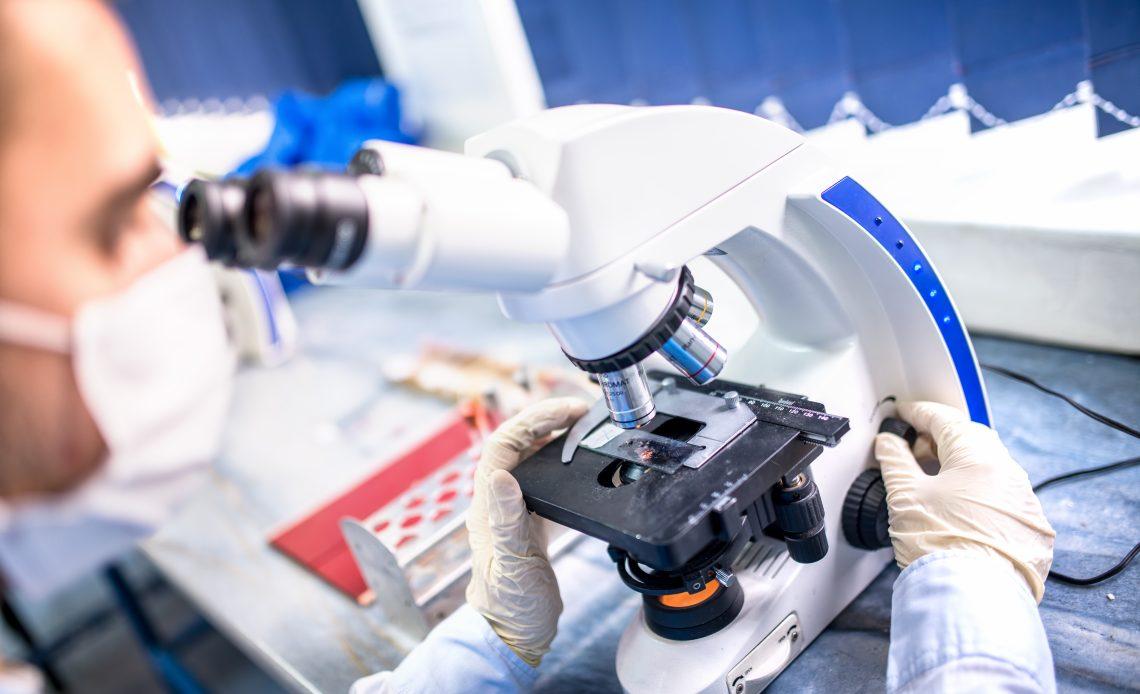 Fotografía de un investigador frente a un microscopio con traje de protección color blanco.