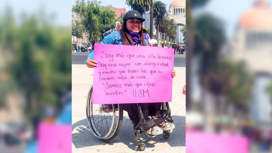 """Fotografía de Jenny Baumed, una joven con discapacidad motriz que está sentada en una silla de ruedas y sostiene un letrero que dice: Soy más que una silla de ruedas, soy una mujer con discapacidad y marcho por todas las que no pueden salir de casa. """"Somos más que cifras invisibles"""" 8M. La chica lleva puesta una gorra color negro y una pañoleta color morado al rededor de su cuello."""