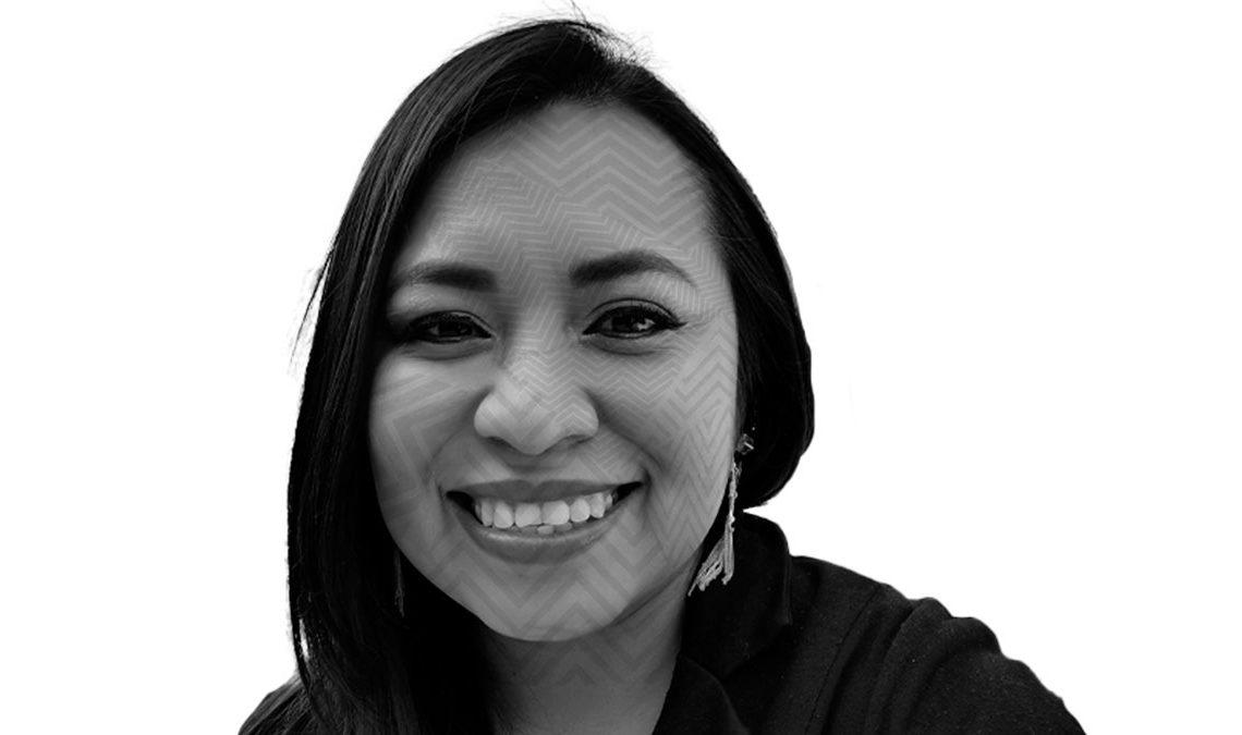 Fotografía con efecto blanco y negro y un patrón de líneas transparentes sobre el rostro de Jenny Bautista, una mujer de edad media, tez latina, cabello lacio que luce sonriente.