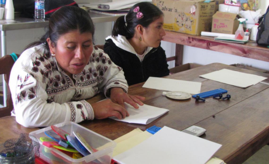 En la fotografía aparece una mujer adulta con tez latina doblando una hoja de papel.