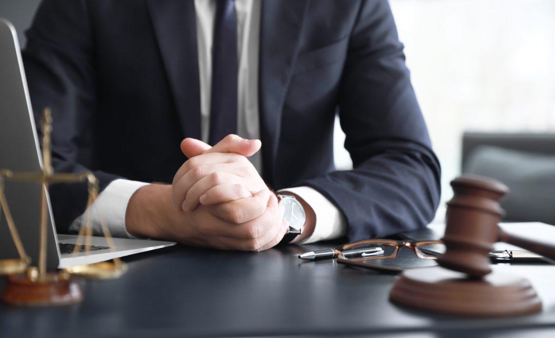 Hombre con corbata y traje sentado frente a su escritorio sobre el cual hay una balanza que representa justicia.