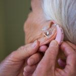 Fotografía en la que se muestra el oído de una mujer mayor de edad con un aparato auditivo en su oído izquierdo.