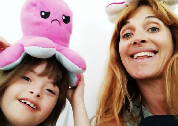 una niña con síndrome de Down un pulpo rosa en la cabeza y una señora que es su mamá con un pulpo rojo en la cabeza