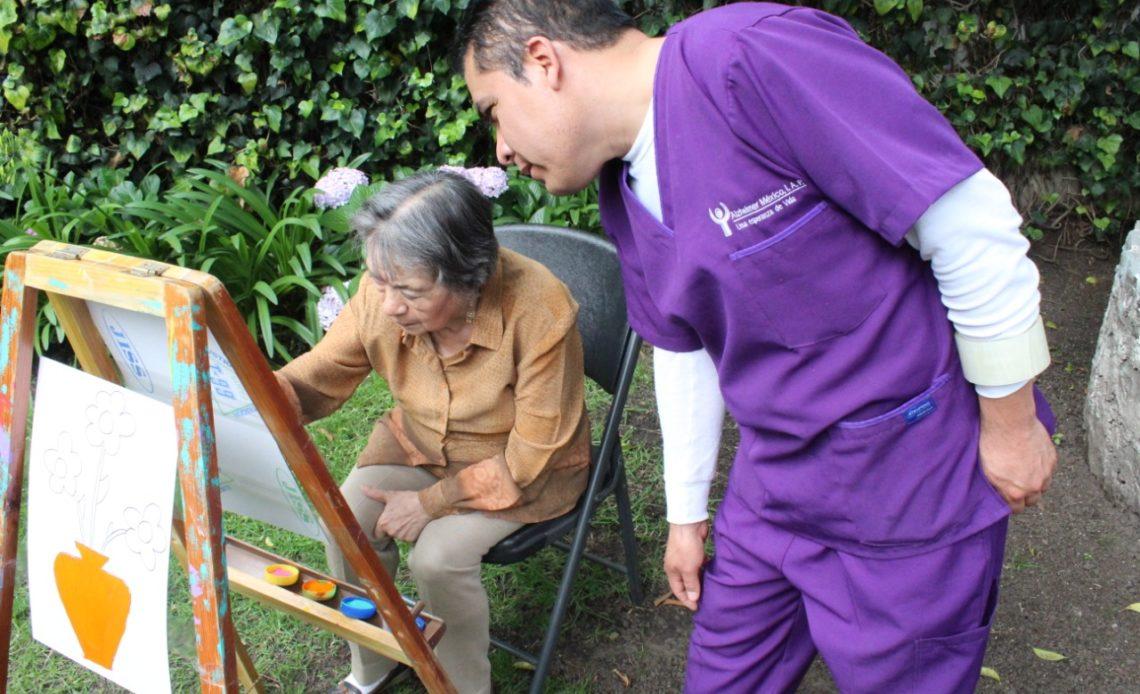 Fotografía en donde se aprecia a una señora de la tercera edad dibujando frente a un caballete mientras es orientada por un cuidador de mediana edad que lleva puesto uniforme de enfermero color morado. Créditos a Beneficiarios de Alzheimer México