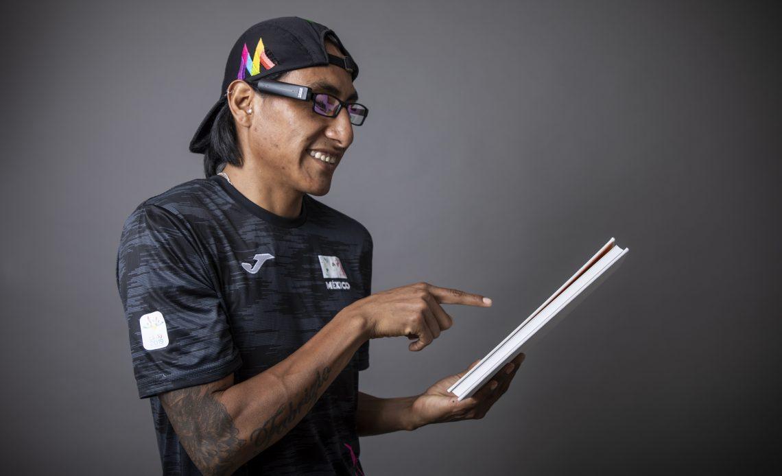 Fotografía de Alejandro Pacheco, un hombre de mediana edad y tez latina, que lleva puesta una gorra color negro, lentes sobre su rostro, sonríe mientras señala y dirige la mirada hacia un libro que sostiene con su mano izquierda.